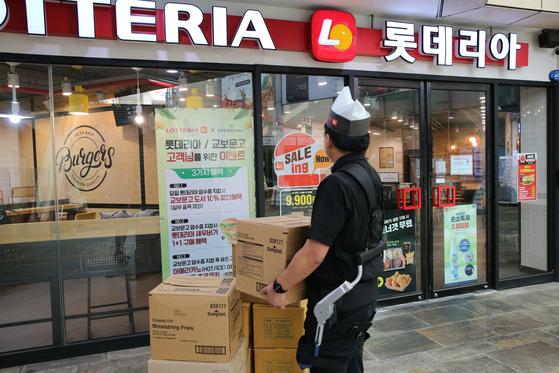 롯데리아 직원이 웨어러블 로봇을 착용한 상태에서 무거운 짐을 운반하고 있다. 사진 롯데GRS