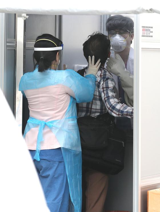 지난 15일 서울 중구 국립중앙의료원에 마련된 선별진료소에서 한 내원객이 코로나19 검사를 받고 있다. 기사 내용과는 관련 없음. 뉴스1