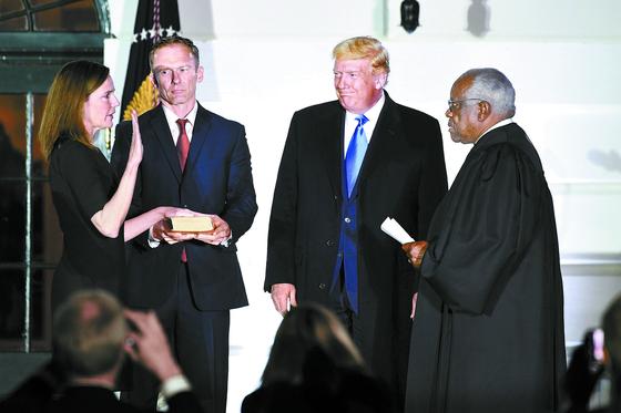 에이미 배럿 신임 대법관이 26일(현지시간) 백악관에서 도널드 트럼프 대통령과 남편 제시 배럿(왼쪽 둘째)이 지켜보는 가운데 클래런스 토머스 대법관 앞에서 선서하고 있다. [AFP=연합뉴스]