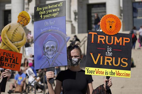 """과거 공화당 텃밭이던 교외 지역 여성들의 표심이 도널드 트럼프 대통령을 떠나고 있다. 지난 17일 미국 솔트레이크 시티에서 한 여성이 """"트럼프는 바이러스이고 당신의 투표는 백신""""이라고 적힌 문구를 들고 있다. [AP=연합뉴스]"""