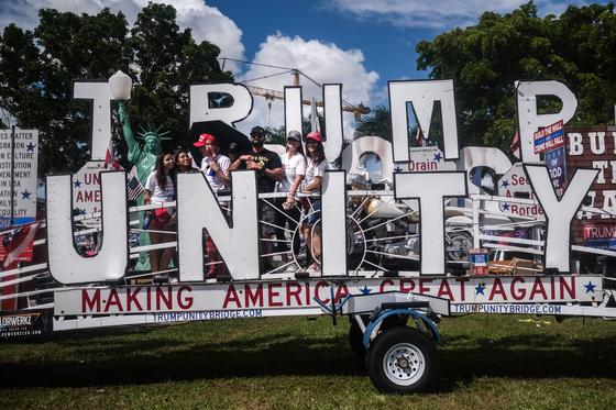 도널드 트럼프 대통령을 열혈 지지하는 극우단체인 '프라우드 보이스' 지도부가 지난 18일 경합주 플로리다 마이애미에서 '트럼프 단결' 플래카드를 내건 트럭을 타고 행진을 벌였다. [EPA=연합뉴스]