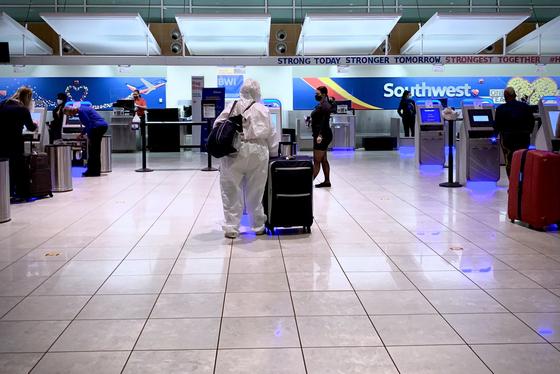 미국 메릴랜드주 볼티모어 워싱턴 국제공항에서 지난 23일(현지시간) 한 여성이 전신 방역복을 입고 탑승수속을 하고 있다. AFP=연합뉴스