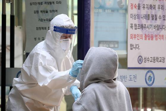 27일 오전 서울 성동구 성수고등학교에 마련된 신종 코로나바이러스 감염증(코로나19) 임시 선별진료소에서 의료진이 학생들을 대상으로 검체 채취를 하고 있다. 뉴스1