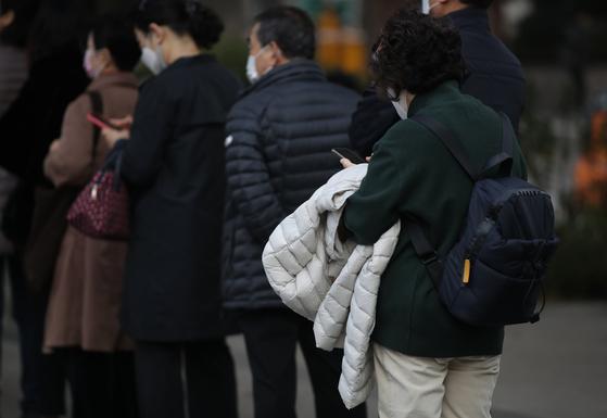 지난 26일 오전 서울 영등포구 여의도역 인근에서 두꺼운 옷을 입은 시민들이 버스를 기다리고 있다. 뉴시스