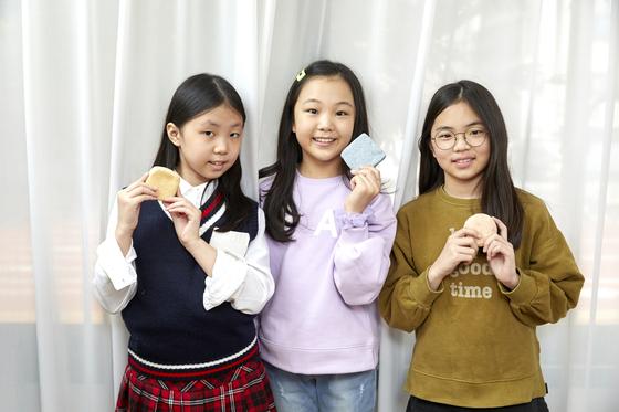 왼쪽부터 김나원 학생기자·윤현지 학생모델·김가은 학생기자가 각자 만든 친환경 샴푸 바를 들고 환하게 웃고 있다.