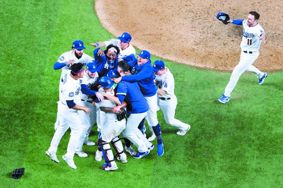 32년 만에 월드시리즈 우승을 확정한 순간, LA 다저스 선수들이 마운드로 몰려들어 얼싸안은 채 기쁨을 나누고 있다. [AFP=연합뉴스]