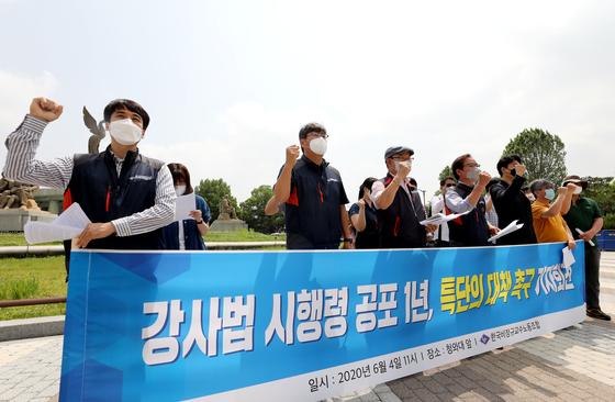 한국비정규교수노동조합 관계자들이 지난 6월 서울 청와대 분수대 앞에서 가진 '강사법 시행령 공포 1년, 특단의 대책 촉구 기자회견'에서 구호를 외치고 있다. 뉴스1