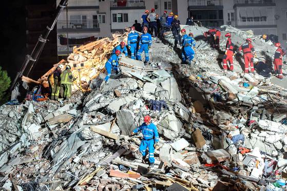 지진으로 무너진 건물에서 구조대가 30일 터키 이즈미르에서 구조 작업을 펼치고 있다. AFP=연합뉴스