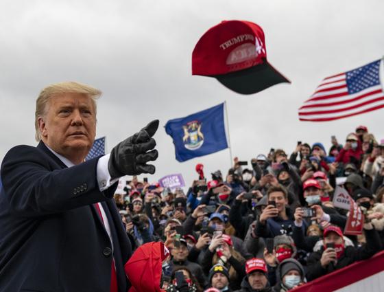 도널드 트럼프 미국 대통령이 지난달 30일(현지시간) 미시간주 워터포드에서 유세를 하는 도중 지지자들에게 자신의 모자를 벗어 던져주고 있다. [AP=연합뉴스]