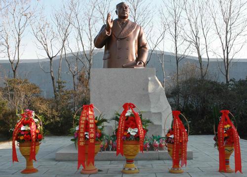 2008 년 3 월 주 탄생 110 주년을 기념하여 주 북한 중국 대사관 함경남도 인민위원회와 화교가 보낸 화환이 동상 앞에 서있다. [신화사]