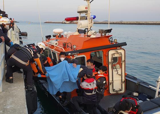 지난달 31일 오전 5시 40분쯤 충남 태안과 보령을 연결하는 원산안면대교 교각을 들이받은 낚싯배에서 해경이 승선원을 구조하고 있다. 이 사고로 3명이 숨지고 19명이 다쳤다. 연합뉴스