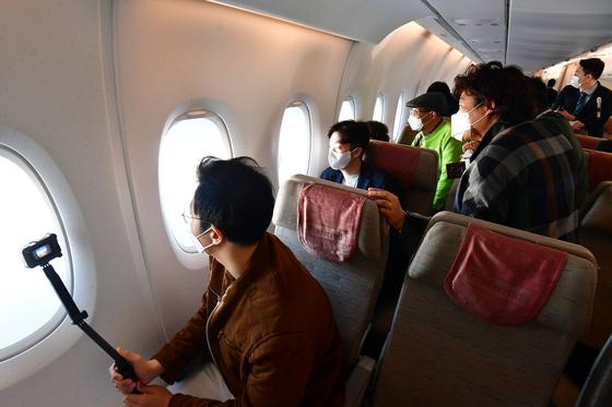 10월 24일 인천공항을 출발한 아시아나항공 'A380 한반도 일주 비행' 항공기에 탑승한 승객들이 한라산 백록담을 내다보고 있다. [연합뉴스]