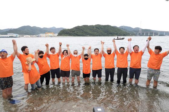 경남 창원시민들이 과거 '오염된 바다' 대명사로 불렸던 마산만 수질이 개선된 것을 알리려 지난 6월 17일 마산만 돝섬 앞바다에서 들어가 퍼포먼스를 하고 있다. 연합뉴스 [창원시 제공]