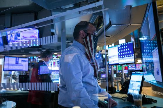 4일 뉴욕 증권거래소에서 한 중개인이 성조기 마스크를 쓴 채 일하고 있다. 이날 다우지수는 1.34%, 나스닥은 3.85% 올랐다. [AP=연합뉴스]