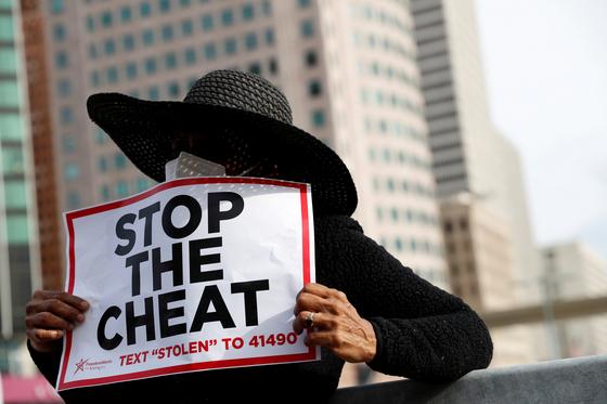 """5일(현지시간) 미시간주 디트로이트에서 2020년 대통령 선거 투표 개표와 관련 """"속임수를 멈춰라""""라는 팻말을 들고 항의하고 있다. [로이터=연합뉴스]"""