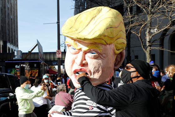 조 바이든 민주당 대선후보의 당선 소식이 전해진 7일(현지시간) 미시간 디트로이트에서 한 시민이 수의를 입은 모습의 트럼프 가면에 주먹을 날리는 포즈를 취했다. [AFP=연합뉴스]