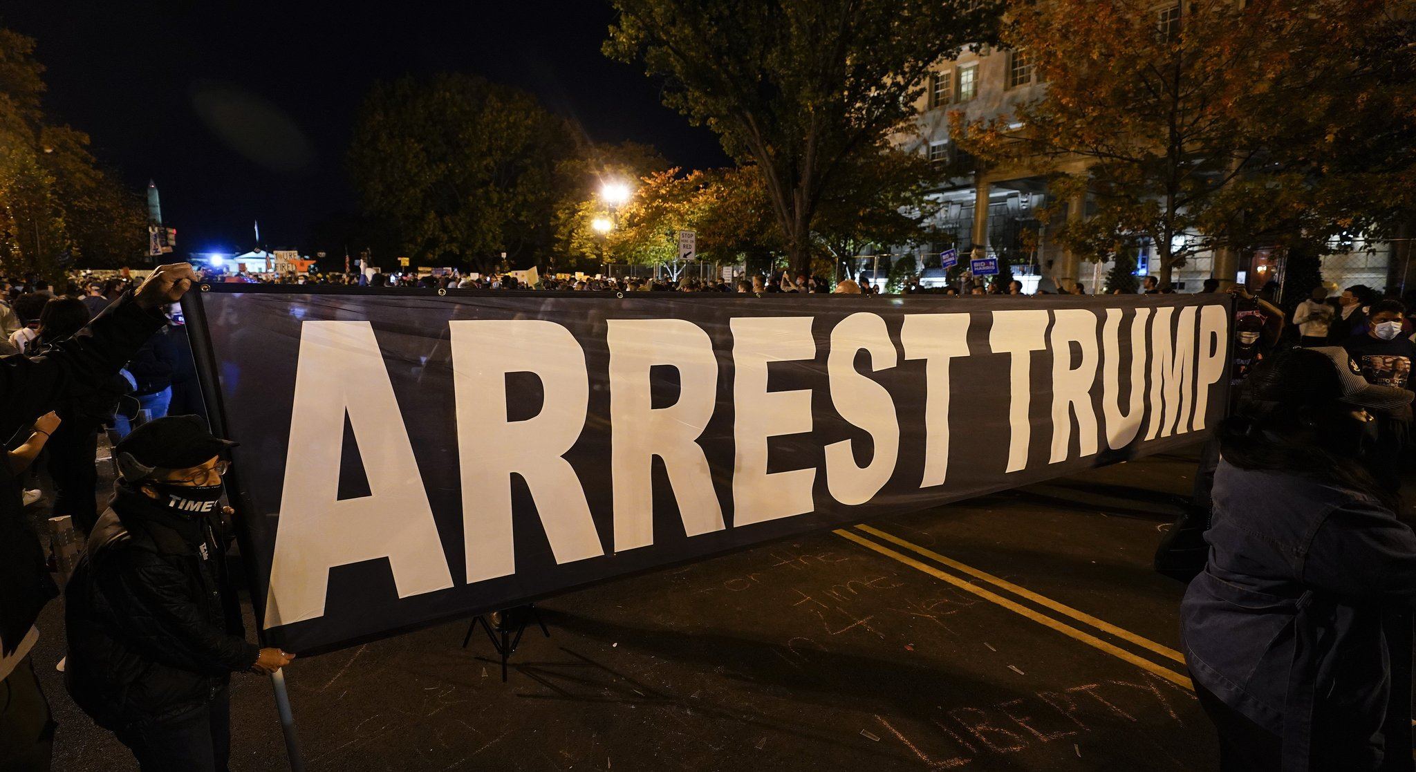 7일 워싱턴DC에서 조 바이든 후보의 승리를 축하하는 지지자들이 '트럼프를 체포하라'는 현수막을 들고 거리를 행진하고 있다. AP=연합뉴스