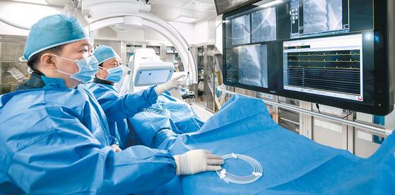 고려대안암병원 유철웅 교수(왼쪽 둘째)가 심혈관 시술실에서 관상동맥 조영술을 진행하고 있다. 심혈관센터는 감염 관리를 위해 모든 시술실에 헤파필터 등 공기 정화 시스템을 적용했다. 김동하 객원기자