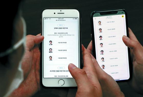 지난 8월 26일 더불어민주당 당대표와 최고위원 선출을 위해 휴대폰으로 모바일 투표하는 더불어민주당 대의원들. [연합뉴스]