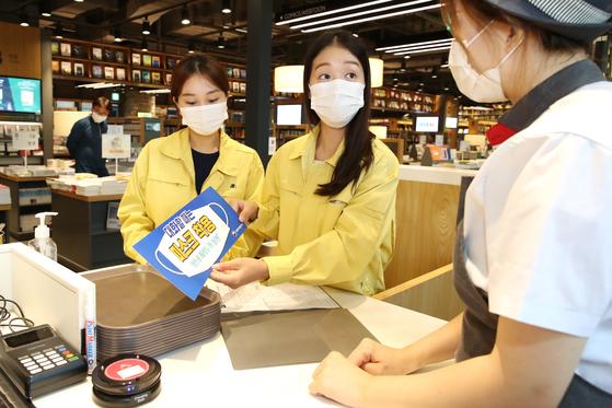 서울 한 구청 직원들이 프랜차이즈 카페에서 마스크 착용 안내문을 설명하고 있다(사진은 기사와 직접적 관련이 없습니다). 뉴스1