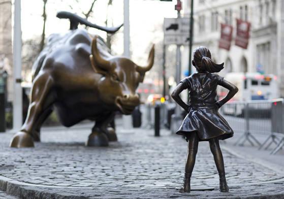 미국 뉴욕증권거래소 앞 두 상징물인 '돌진하는 황소'상과 '두려움 없는 소녀'상. AP=연합뉴스