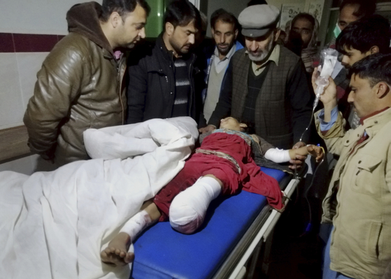 On the 13th, residents gather near an injured child in Kashmir, Pakistan.  Associated Press = Yonhap News