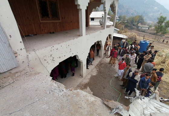 On the 13th, in a village in Kashmir, Pakistan, residents gather in front of a partially collapsed building.  Reuters = Yonhap News