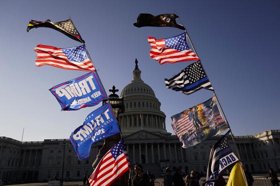 트럼프 대통령 지지자들이 든 깃발이 14일 미국 의사당을 배경으로 펄럭이고 있다. AP=연합뉴스