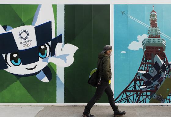 한 도쿄 시민이 올림픽 홍보 게시물 앞을 지나고 있다. [AP=연합뉴스]