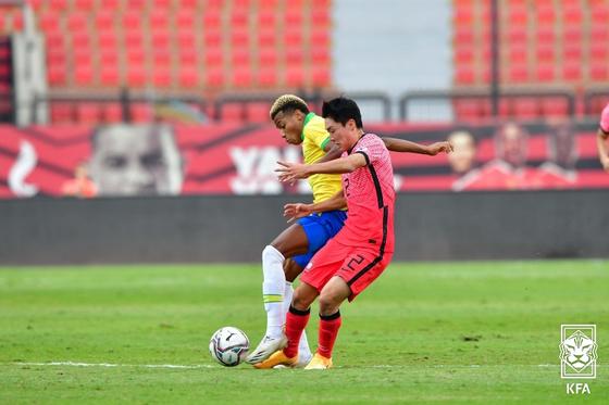 올림픽축구대표팀 강윤성이 브라질 선수와 볼을 다투고 있다. 한국은 도쿄올림픽 우승후보 브라질에 1-3으로 졌다. [사진 대한축구협회]