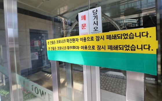 지난 5일 충남 천안시 신부동의 한 건물 정문이 굳게 닫혀 있다. 이 건물에 입주한 신한생명 천안콜센터에서 코로나19 확진자가 무더기로 나와 방역 당국이 역학조사에 나왔다. 연합뉴스