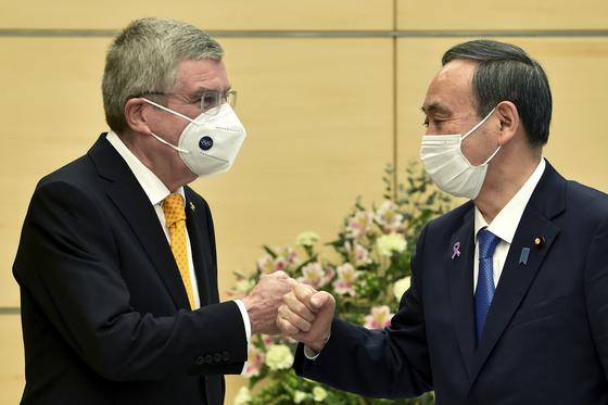 스가 요시히데 (오른쪽) 일본 총리와 토마스 바흐 IOC 위원장이 16일 도쿄 총리관저에서 만나 주먹으로 인사를 나누고 있다. [AP=연합뉴스]