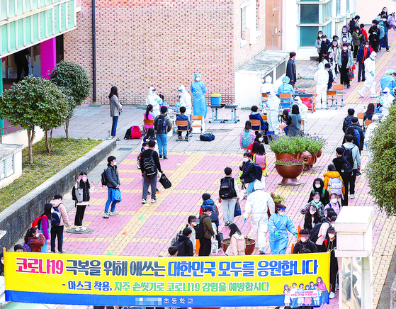 16일 코로나19 신규 확진자가 223명 늘어 사흘 연속 200명을 넘었다. 이날 광주광역시 북구의 한 초등학교에 마련된 선별진료소에서 학생들이 검사를 받기 위해 줄을 서고 있다. 프리랜서 장정필