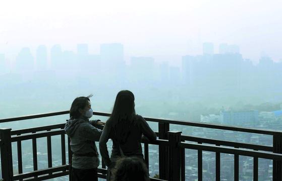 서울 지역에 올 가을 첫 초미세먼지 주의보(농도 '매우나쁨')가 내려진 15일 시민들이 남산순환도로 전망대에서 희뿌연 도심을 바라보고 있다. 김상선 기자