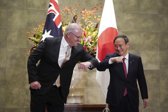 스가 요시히데 일본 총리(오른쪽)와 스콧 모리슨 호주 총리가 지난 17일 도쿄의 총리관저에서 팔꿈치로 인사를 나누고 있다. [AP=연합뉴스]