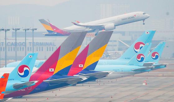 지난 18일 오전 인천국제공항 주기장에 세워진 대한항공과 아시아나항공 여객기 뒤로 아시아나항공 여객기가 이륙하고 있다. 연합뉴스