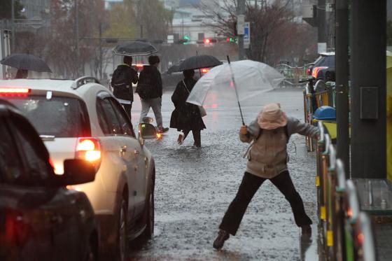 서울,경기,인천 등 수도권 지역에 호우주의보가 발령된 19일 오전 서울 상암동 건널목에서 시민들이 길을 건너고 있다. 우상조 기자