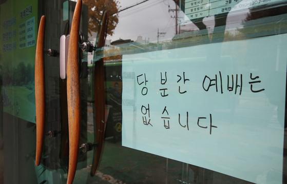 정부가 19일부터 수도권의 사회적 거리두기 단계를 1단계에서 1.5단계로 격상하기로 한 지난 17일 서울 노량진의 한 교회에 당분간 예배가 없다는 안내문이 부착돼 있다. 우상조 기자