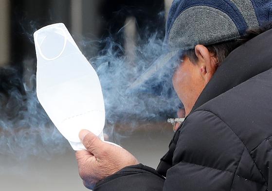 9일 서울역 광장에서 한 시민이 한 손에 마스크를 들고 담배를 피고 있다. [뉴스1]