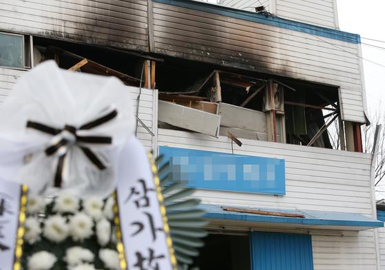 20일 오전 인천시 남동구 고잔동 한 화장품 제조업체 공장 앞에 근조 화환이 놓여 있다. 전날 이 건물 2층에서 불이 나 20~50대 남성 3명이 숨지고 소방관 1명과 근로자 5명 등 모두 6명이 다쳤다. 연합뉴스