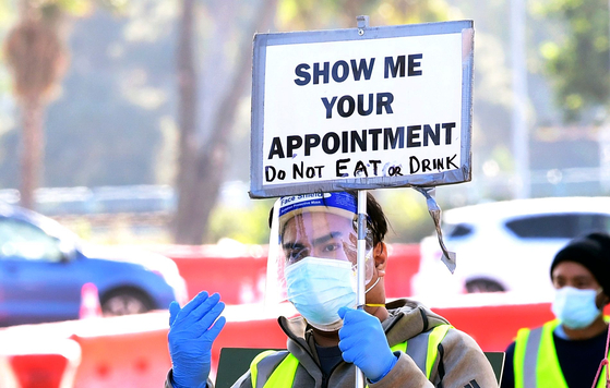 12일(현지시간) 미국 LA의 코로나 진단 검사장에서 한 자원봉사자가 '예약증을 보여달라'는 안내판을 들고 있다. AFP=연합뉴스