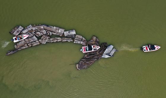 1일 강원 춘천시 의암호에서 지난달 6일 의암댐으로 떠내려가 파손된 인공수초섬 일부를 중도 배터로 옮기는 작업을 하고 있다.연합뉴스
