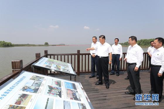 시진핑 중국 국가 주석이 수해 피해 지역을 시찰하고있다. 뒷 배경으로 펼쳐지는 강 온화한 모습이다. 때 코멘트를 비롯해 함께 시찰하는 사람들도 신발을 신고있다. [신화망]