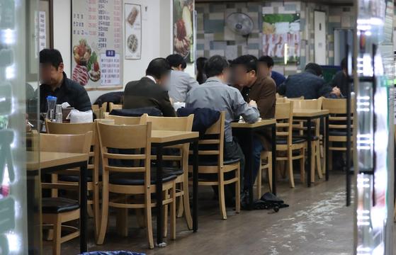 정부가 코로나19 확산 방지를 위해 수도권과 광주, 강원 일부 지역에 사회적 거리두기 1.5단계 격상 조처를 내린 가운데 19일 서울의 한 식당에서 직장인들이 평소처럼 점심식사를 하고 있다. 뉴시스