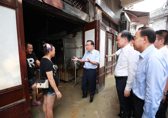 지난 8 월 리 克強 총리 (가운데)가 충칭 수해 피해 지역 주민들과 이야기를 나누고있다. 흙탕물에 발목이 잠긴에서 장화를 신은 리 총리의 모습. [중앙인민정부 홈페이지]