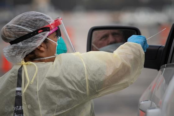 미국에서 21일(현지시간) 코로나 19 누적 감염자가 1200만명을 돌파했다. 지난 20일 텍사스에서 의료진이 드라이브 스루 방식으로 코로나 검사를 하고 있다. [로이터=연합뉴스]