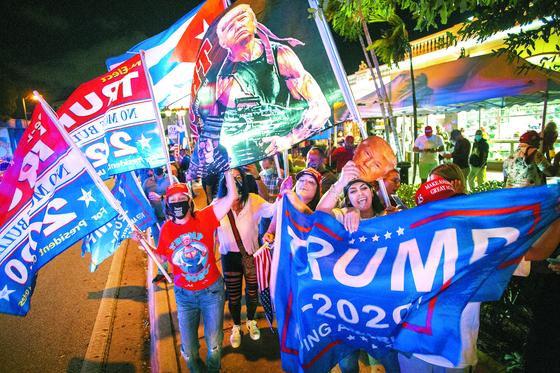 지난 3일 도널드 트럼프 대통령 지지자들이 플로리다 마이애미의 한 식당 앞에서 깃발을 흔들며 응원하고 있다. [EPA=연합뉴스]