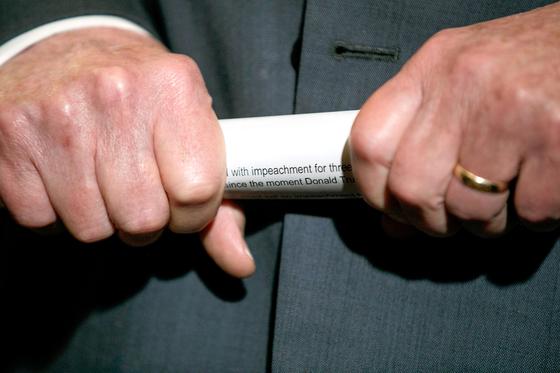 미국 상원 다수당인 공화당의 미치 매코널 원내대표가 2019년 10월 29일 민주당이 공식 발의한 트럼프 대통령에 대한 탄핵 결의안 서류를 말아 쥐고 기자들의 질문을 듣고 있다. [AP=연합뉴스]