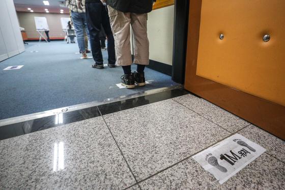 제21대 국회의원 선거일인 4월 15일 오전 서울 성북구 북한산국립공원 탐방안내소에 마련된 정릉4동 제4투표소 바닥에 사회적 거리두기를 위한 안내문이 붙어 있다. 사진은 기사 본문과 관련 없음. 뉴스1