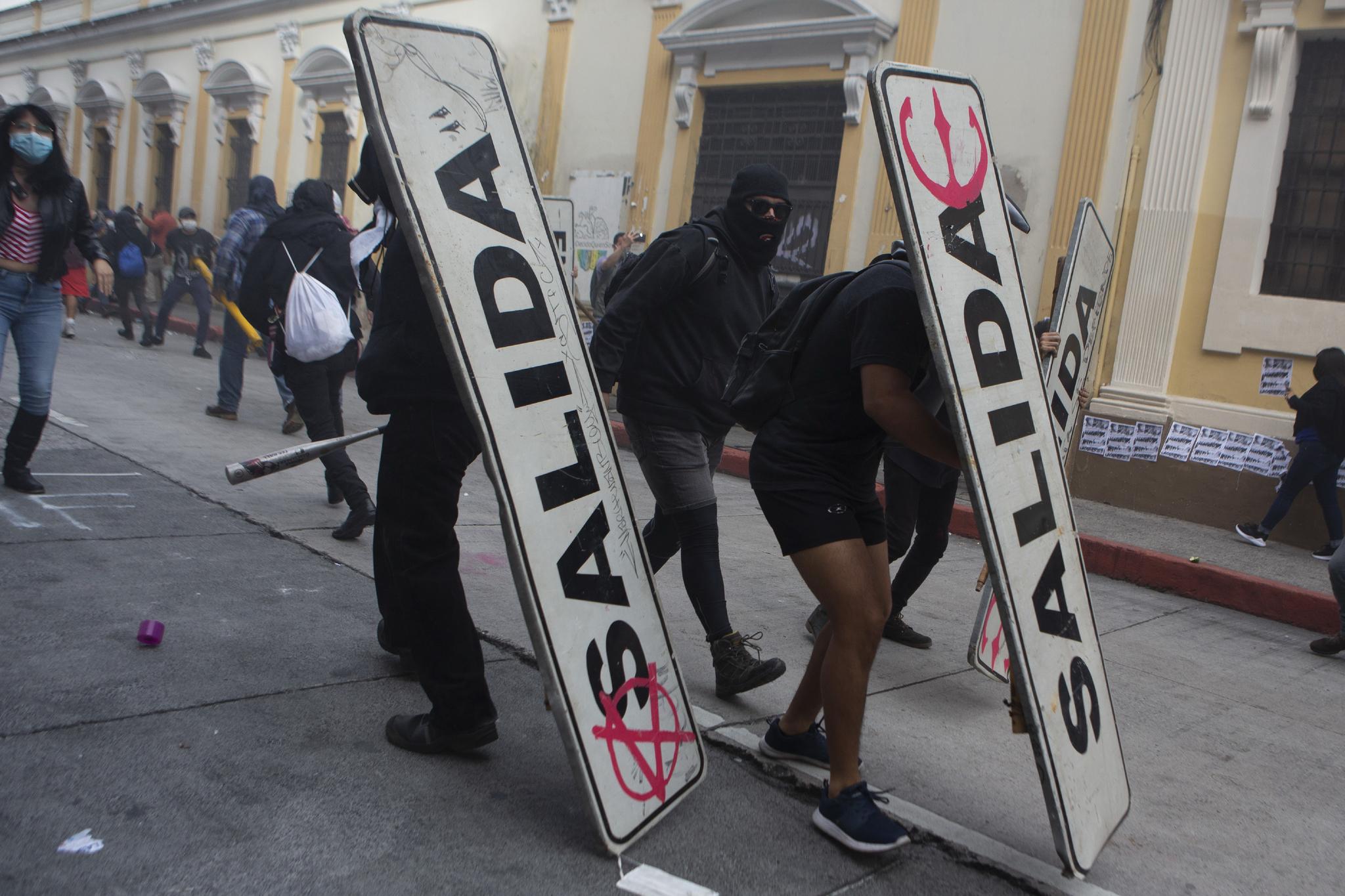 시위대가 '출구'안내판을 방패로 시위를 벌이고있다. AP 통신